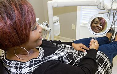 Dentures patient looking at self in mirror